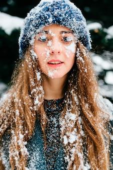 Retrato divertido del invierno de la muchacha morena de pelo largo hermosa con su cara y pelo cubiertos de nieve.