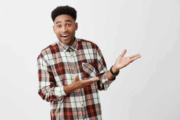 Retrato de divertido joven hermoso de piel oscura con peinado afro en camisa casual sonriendo, mostrando la pared blanca con las manos con expresión emocionada y feliz
