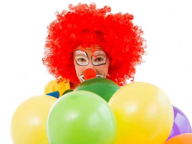 Retrato de un divertido payaso juguetón en peluca roja con globos.
