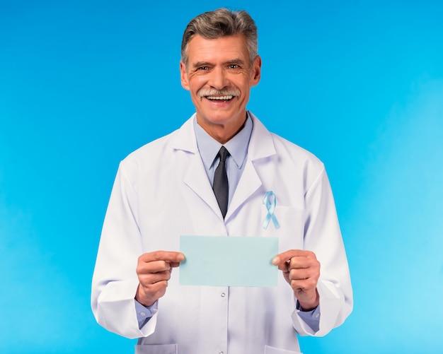 Retrato de un doctor con una cinta azul en la pared azul.