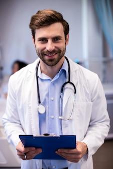 Retrato del doctor hombre sonriente con portapapeles