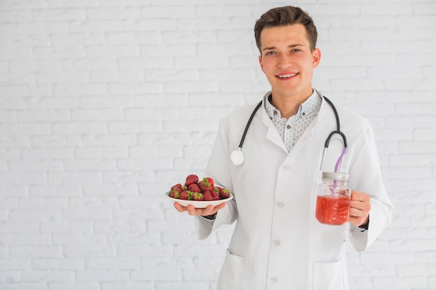 Retrato del doctor de sexo masculino que sostiene las frutas y el smoothie de la fresa