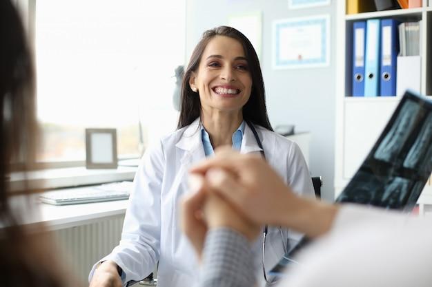 Retrato del doctor sonriente que sostiene la radiografía y que informa buenas noticias a los pacientes.