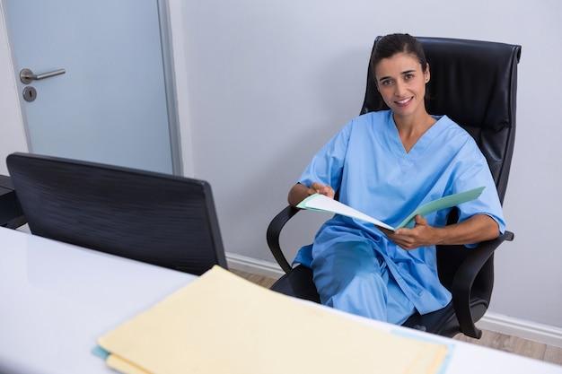 Retrato del doctor sonriente sosteniendo el archivo mientras está sentado en una silla