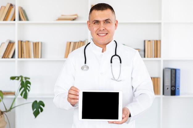 Retrato del doctor sonriente sosteniendo foto maqueta