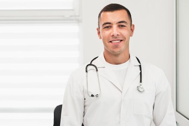 Retrato del doctor sonriente vistiendo túnica blanca