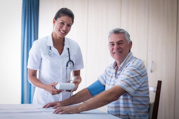 Retrato de doctora comprobando la presión arterial del hombre senior