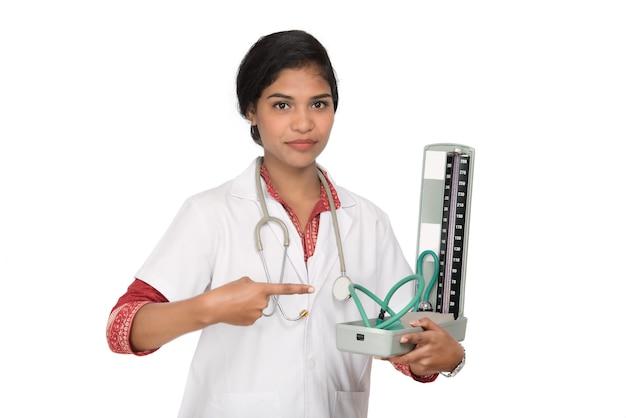Retrato de una doctora con instrumento de presión arterial y estetoscopio sobre fondo blanco.