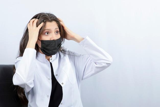 Retrato de doctora en máscara médica y bata blanca discutiendo con alguien.
