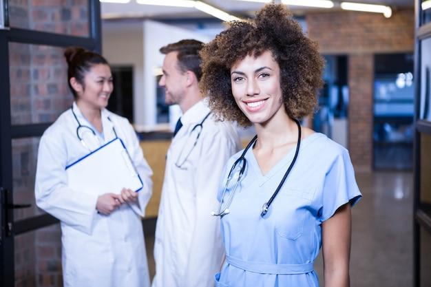 Retrato de doctora sonriendo y colegas de pie detrás y discutiendo