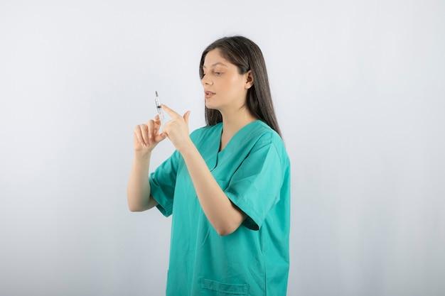 Retrato de doctora sosteniendo una jeringa grande. .