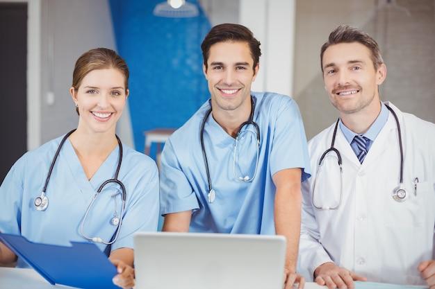 Retrato de doctores alegres con laptop y portapapeles