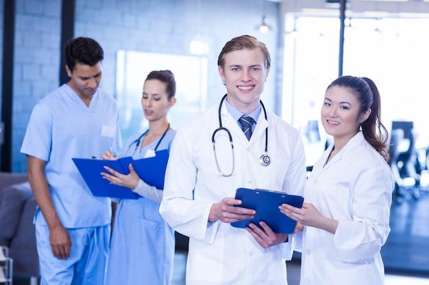 Retrato de los doctores que miran informe médico y que sonríen