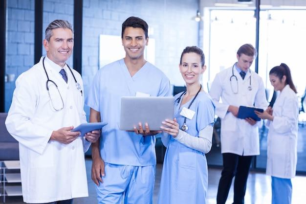 Retrato de los doctores que sonríen mientras que usa el ordenador portátil y la tableta digital en hospital