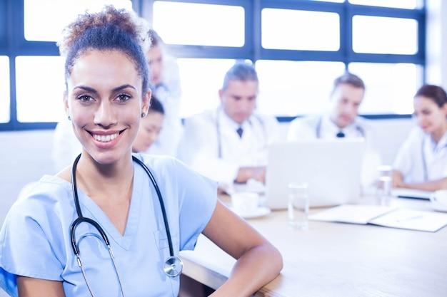 Retrato de doctores sonrientes y otro doctor discutiendo detrás en la sala de conferencias