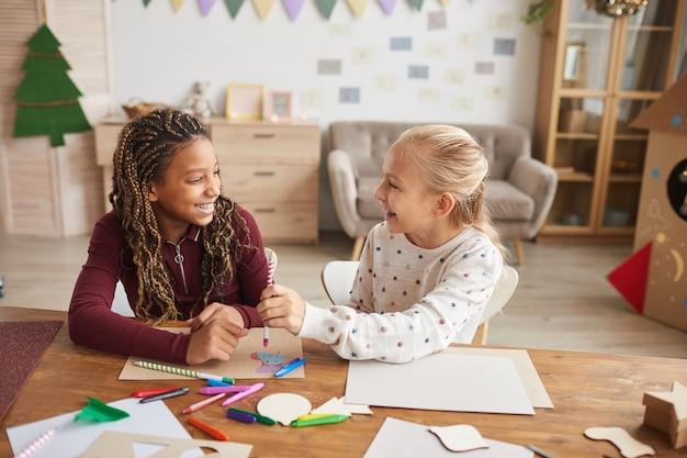 Retrato de dos adolescentes riendo disfrutando de la elaboración y la pintura juntos mientras se sientan en el escritorio en la sala de juegos decorada, espacio de copia