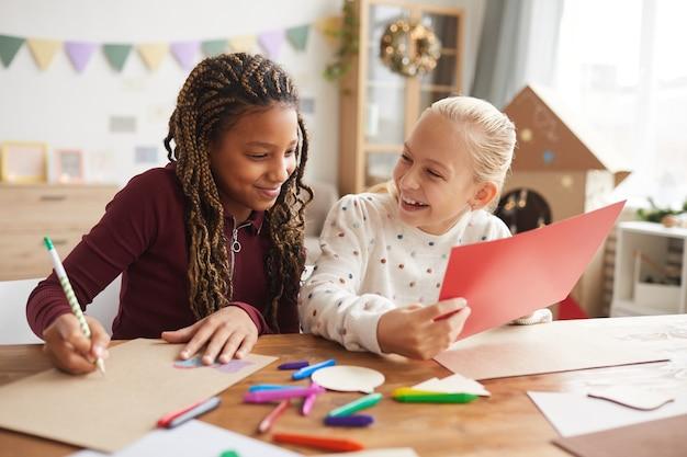 Retrato de dos adolescentes riendo disfrutando de la elaboración y la pintura juntos mientras se sientan en un escritorio en la sala de juegos decorada