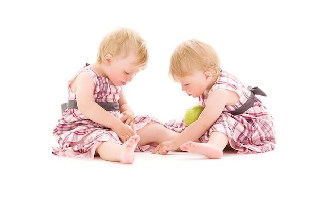 Retrato de dos adorables gemelos sobre pared blanca