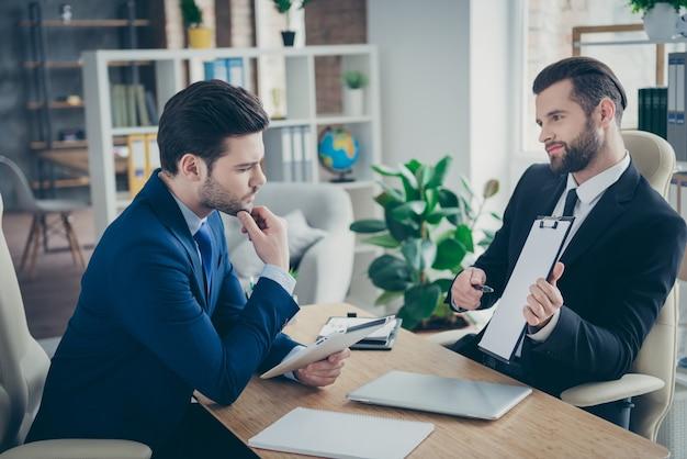 Retrato de dos agradable atractivo guapo elegante imponente de moda hombres economista agente financiero corredor firma contrato gestión de recursos humanos en la estación de lugar de trabajo interior blanco claro