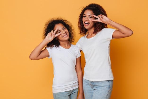 Retrato de dos alegres hermanas africanas de pie