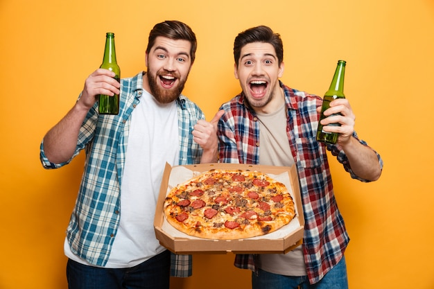 Retrato de dos alegres jóvenes bebiendo cerveza con pizza