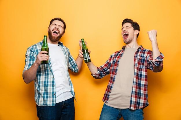 Retrato de dos alegres jóvenes sosteniendo botellas de cerveza