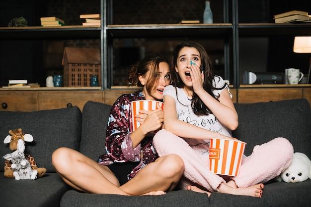 Retrato de dos amigas asustadas viendo la televisión