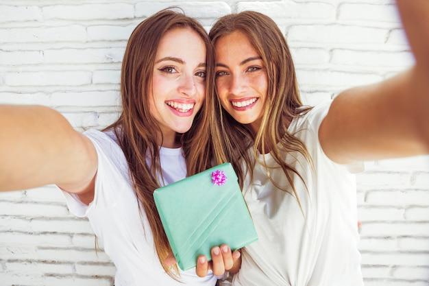 Retrato de dos amigas felices con caja de regalo