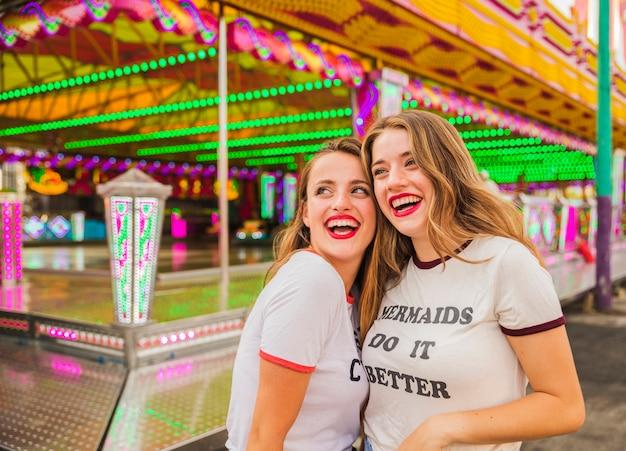 Retrato de dos amigas felices divirtiéndose en el parque de atracciones