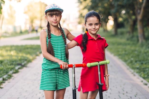 Retrato de dos amigas con su patinete scooter