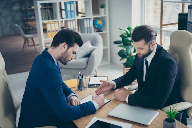 Retrato de dos bonitos atractivos guapos con clase elegantes hombres de moda economista firmando contrato de trabajo oferta de contratación en la estación de lugar de trabajo interior blanco claro en el interior