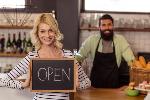 Retrato de dos camareros casuales sosteniendo un tablero escrito abierto