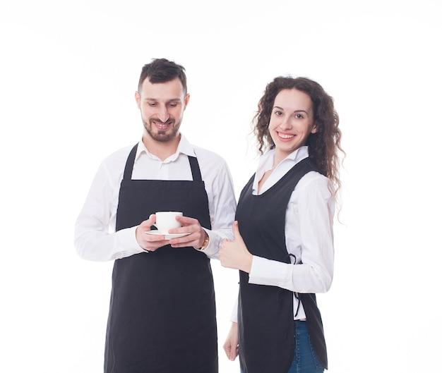Retrato de dos camareros en el fondo blanco. pareja trabajando en la cafetería.