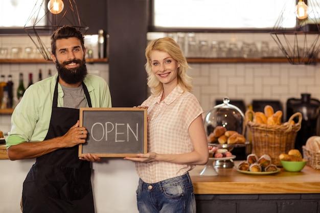 Retrato de dos camareros sosteniendo un tablero escrito abierto
