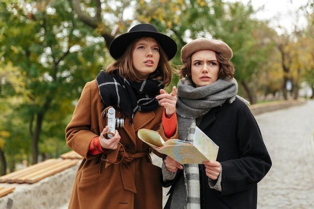 Retrato de dos chicas confundidas vestidas con ropa de otoño