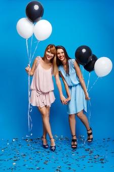 Retrato de dos chicas descansando en la fiesta sobre la pared azul