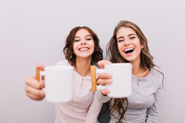 Retrato de dos chicas divertidas en pijama divirtiéndose en la pared gris. ellos estiran tazas blancas y sonríen.
