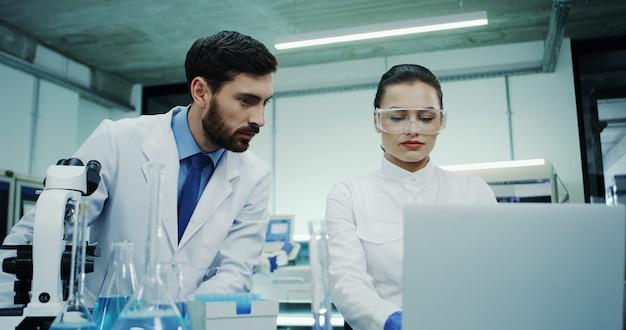 Retrato de los dos científicos de laboratorio caucásicos, hombre y mujer, hablando mientras él trabajaba en el microscopio y ella en la computadora portátil. de cerca.