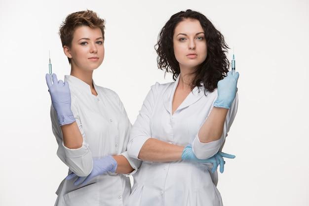 Retrato de dos cirujanos mujeres mostrando jeringas
