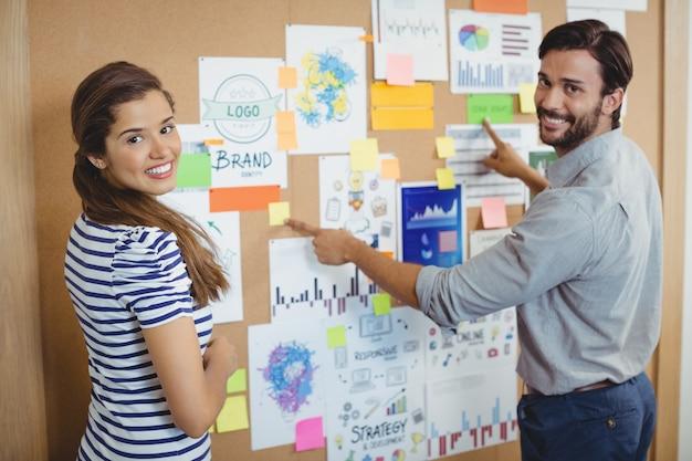 Retrato de dos ejecutivos de negocios discutiendo sobre el tablón de anuncios