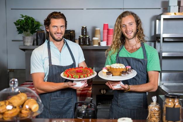 Retrato de dos empleados masculinos sosteniendo el postre en el soporte de la torta en el mostrador