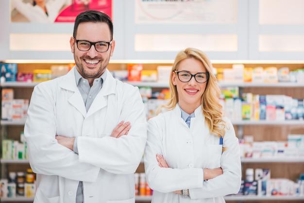 Retrato de dos farmacéuticos jovenes hermosos en el lugar de trabajo.