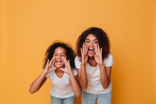 Retrato de dos hermanas afroamericanas alegres gritando