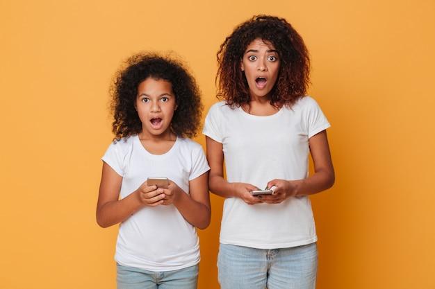 Retrato de dos hermanas afroamericanas sorprendidas con teléfonos inteligentes
