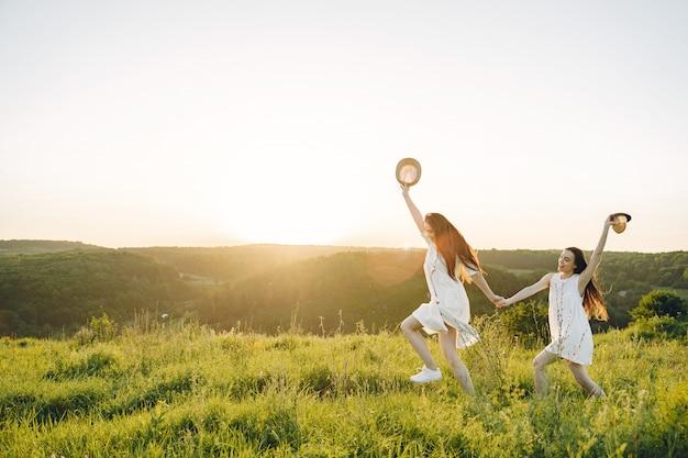 Retrato de dos hermanas en vestidos blancos con pelo largo en un campo