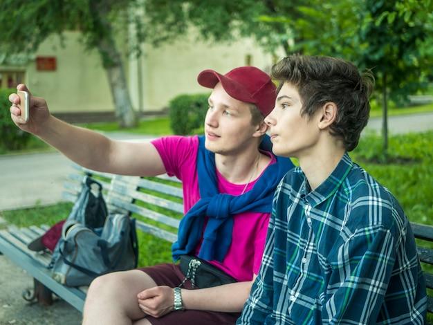 Retrato de dos hermanos jóvenes atractivos haciendo un autorretrato usando un teléfono al aire libre