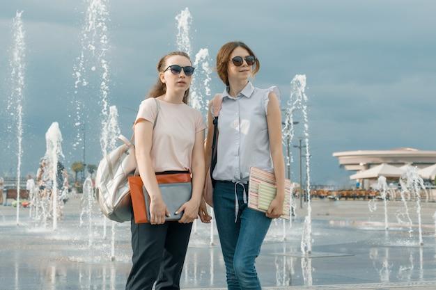 Retrato de dos hermosas chicas jóvenes con mochilas cerca de una fuente