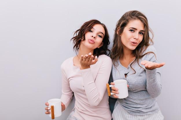 Retrato de dos hermosas chicas en pijama con tazas blancas sobre pared gris. envían besos.