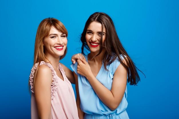 Retrato de dos hermosas chicas sobre pared azul