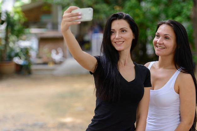 Retrato de dos hermosas mujeres felices tomando selfie juntos al aire libre